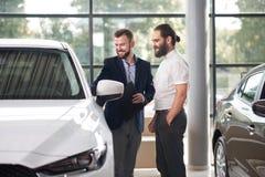 Manager die aan klant van de witte auto van het autocentrum tonen royalty-vrije stock foto's