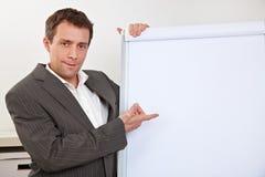 Manager die aan lege flipchart richt stock afbeelding