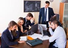 Manager die aan werknemers op groepsvergadering schreeuwen royalty-vrije stock afbeelding