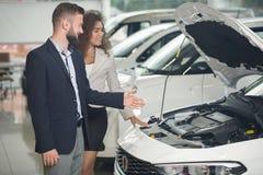Manager die auto tonen onder kap aan cliënt in autocentrum royalty-vrije stock afbeeldingen