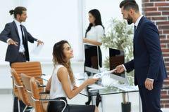 Manager die de werknemer het document overhandigen stock afbeelding
