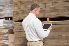 Manager die digitale tablet in pakhuis gebruiken royalty-vrije stock foto