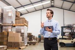 Manager die digitale tablet in pakhuis gebruiken stock afbeelding