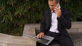 Manager die door smartphone spreken en met laptop buiten in langzame motie werken stock footage