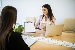 Manager die een werknemer in haar modern bureau interviewen royalty-vrije stock afbeeldingen