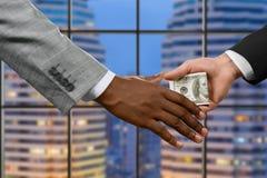 Manager die geld overhandigen dichtbij venster stock foto