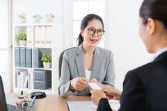 Manager die het jonge adreskaartje van het verkoopmeisje geven stock foto