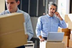 Manager die Hoofdtelefoon in het Pakhuis van de Distributie met behulp van Royalty-vrije Stock Afbeelding