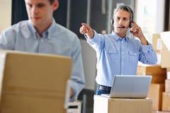Manager die Hoofdtelefoon in het Pakhuis van de Distributie met behulp van stock fotografie
