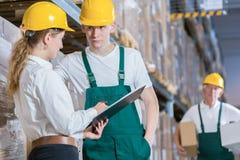 Manager die met opslagarbeider spreken stock afbeelding