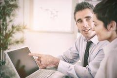 Manager die op iets aan zijn secretaresse op laptop richten royalty-vrije stock fotografie