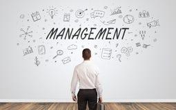 Manager die in twijfel aan een muur met bedrijfsconcept kijken stock afbeelding