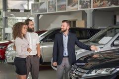 Manager die van autocentrum auto tonen aan cliënten royalty-vrije stock fotografie