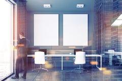 Manager die in venster van grijs bureau, affiches kijken Stock Foto's