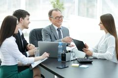 Manager discussing work issues with his assistants behind a Desk. Photo with place for text stock photos