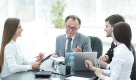 Manager discussing work issues with his assistants behind a Desk. Photo with place for text stock images