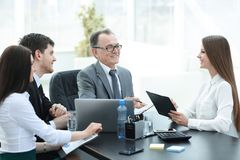Manager discussing work issues with his assistants behind a Desk. Photo with place for text stock photo