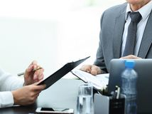 Manager discussing work issues with his assistants behind a Desk. Photo with place for text royalty free stock images