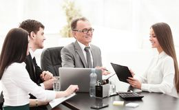 Manager discussing work issues with his assistants behind a Desk. Photo with place for text royalty free stock photos