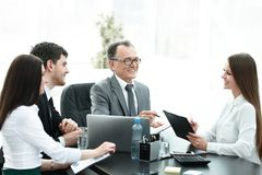 Manager discussing work issues with his assistants behind a Desk. Photo with place for text royalty free stock image
