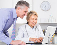 Manager and doctor reading news. Mature doctor and manager discussing news information on clinic site royalty free stock images