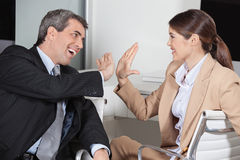 Manager and employee giving high. Manager and employee in the office giving high five to each other Stock Image