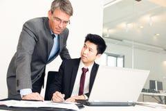 Manager And Employee Looking an den Dokumenten Stockbilder