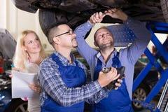 Manager en bemanning die controle omhoog van gebroken auto doen stock fotografie