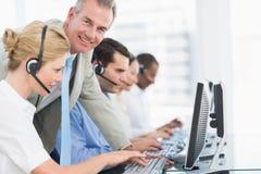 Manager en stafmedewerkers met hoofdtelefoons die computers met behulp van Stock Afbeelding