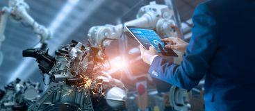 Manager engineer controlling automation robot arms machine. Manager engineer check and control automation robot arms machine in intelligent factory industrial on royalty free stock image
