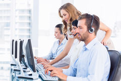 Manager and executives with headsets using computers Royalty Free Stock Image