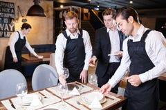 Manager explaining table setting to waiters stock photography