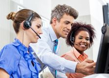 Manager Explaining To Employees In Call Center. Manager explaining something to his employees in call center Royalty Free Stock Images