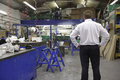 Manager on factory floor. Young manager looking at empty factory floor with hands on hip stock images