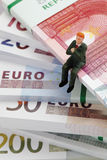 Manager figurine sitting on stack of euro notes Royalty Free Stock Photo
