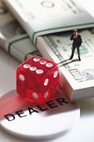 Manager figurine standing on bundle of 100 us dollar notes with dice Royalty Free Stock Photo