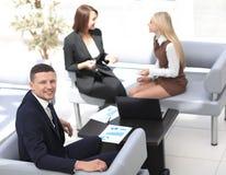 Manager Finance, das mit Dokumenten auf dem Hintergrund von Kollegen arbeitet Lizenzfreie Stockfotografie