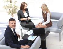 Manager Finance, das mit Dokumenten auf dem Hintergrund von Kollegen arbeitet Lizenzfreies Stockbild