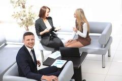 Manager Finance, das mit Dokumenten auf dem Hintergrund von Kollegen arbeitet stockfotografie