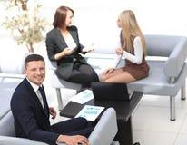 Manager Finance, das mit Dokumenten auf dem Hintergrund von Kollegen arbeitet lizenzfreie stockbilder