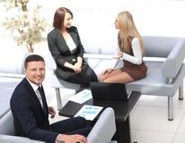 Manager Finance, das mit Dokumenten auf dem Hintergrund von Kollegen arbeitet lizenzfreie stockfotos
