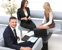 Manager Finance, das mit Dokumenten auf dem Hintergrund von Kollegen arbeitet stockfotos