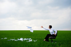 Manager fling documents. Manager sitting on armchair and fling documents on green meadow royalty free stock images