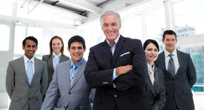 Manager with folded arms accompanied by his team Stock Photos