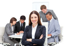 Manager with folded arms in front on his team. Confident manager with folded arms in front on her team in a meeting stock image