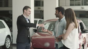 The manager gives the keys from car to a young couple. Young couple choose the car in car showroom. The manager in suit gives the keys from car to a swarthy man stock video footage