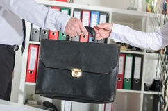Manager giving his briefcase to his secretary Royalty Free Stock Photo