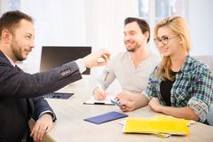 Manager giving key to couple royalty free stock photography