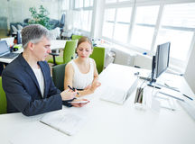 Manager giving order to assistant in office. Manager giving order to his assistant in business office Stock Images