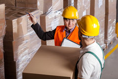 Manager giving worker instruction in warehouse. Manager giving worker instruction about loads storage in warehouse royalty free stock photography